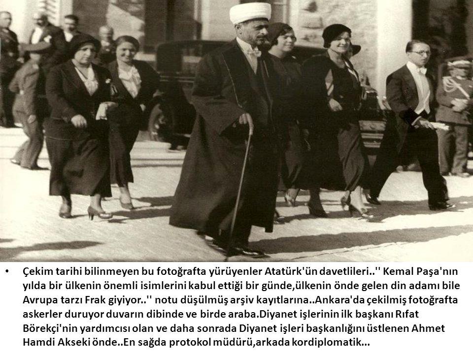 Çekim tarihi bilinmeyen bu fotoğrafta yürüyenler Atatürk ün davetlileri.. Kemal Paşa nın yılda bir ülkenin önemli isimlerini kabul ettiği bir günde,ülkenin önde gelen din adamı bile Avrupa tarzı Frak giyiyor.. notu düşülmüş arşiv kayıtlarına..Ankara da çekilmiş fotoğrafta askerler duruyor duvarın dibinde ve birde araba.Diyanet işlerinin ilk başkanı Rıfat Börekçi nin yardımcısı olan ve daha sonrada Diyanet işleri başkanlığını üstlenen Ahmet Hamdi Akseki önde..En sağda protokol müdürü,arkada kordiplomatik...