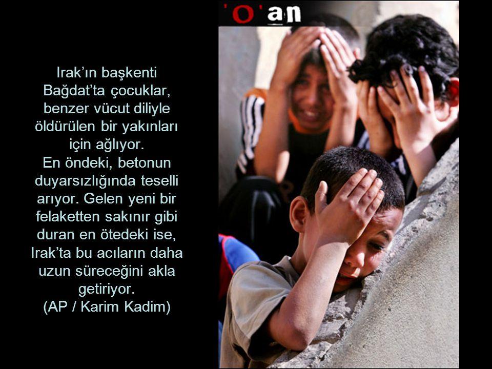 Irak'ın başkenti Bağdat'ta çocuklar, benzer vücut diliyle öldürülen bir yakınları için ağlıyor.