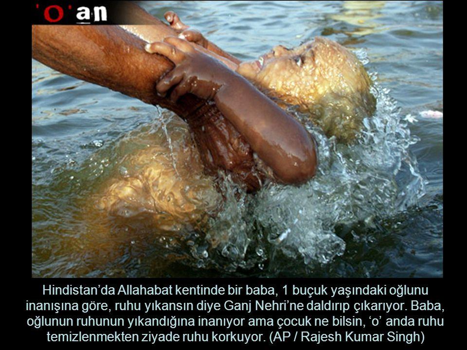 Hindistan'da Allahabat kentinde bir baba, 1 buçuk yaşındaki oğlunu inanışına göre, ruhu yıkansın diye Ganj Nehri'ne daldırıp çıkarıyor.