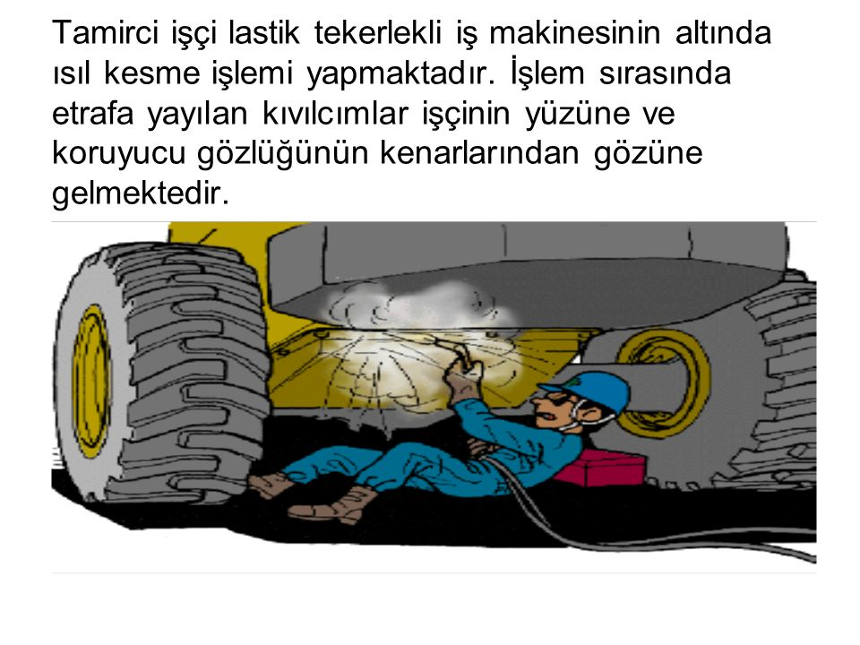 Tamirci işçi lastik tekerlekli iş makinesinin altında ısıl kesme işlemi yapmaktadır.