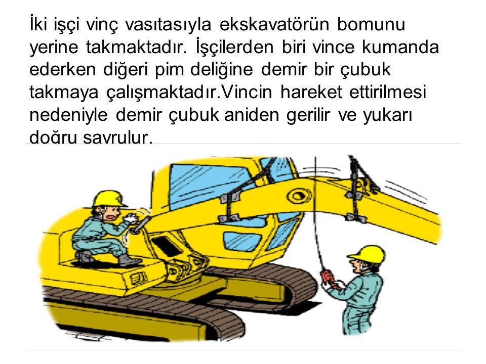 İki işçi vinç vasıtasıyla ekskavatörün bomunu yerine takmaktadır