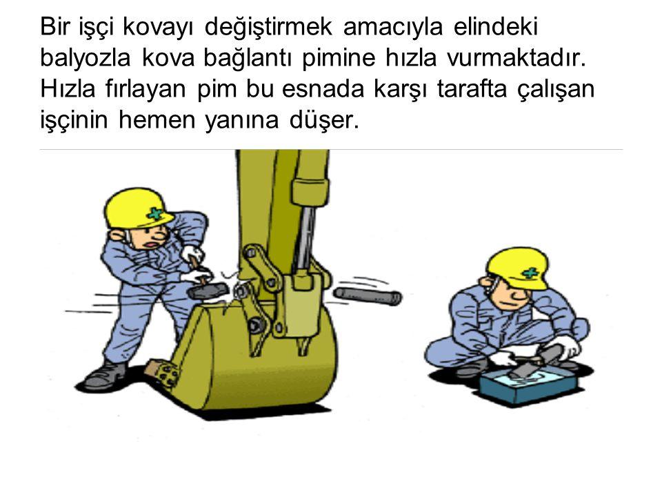 Bir işçi kovayı değiştirmek amacıyla elindeki balyozla kova bağlantı pimine hızla vurmaktadır.