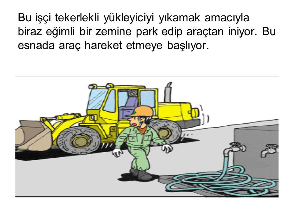 Bu işçi tekerlekli yükleyiciyi yıkamak amacıyla biraz eğimli bir zemine park edip araçtan iniyor.
