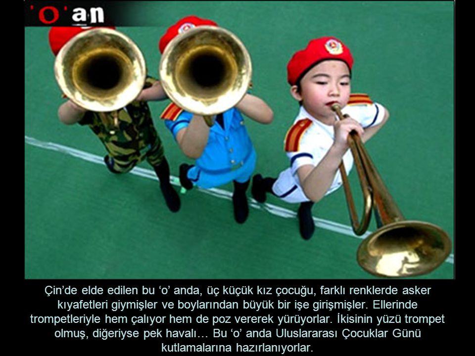 Çin'de elde edilen bu 'o' anda, üç küçük kız çocuğu, farklı renklerde asker kıyafetleri giymişler ve boylarından büyük bir işe girişmişler.