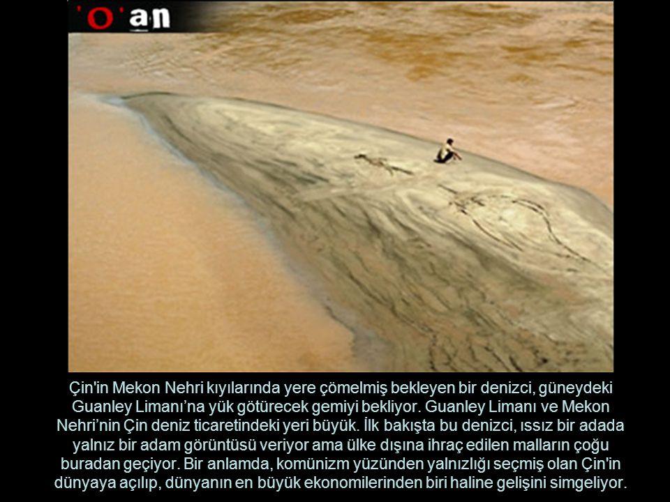 Çin in Mekon Nehri kıyılarında yere çömelmiş bekleyen bir denizci, güneydeki Guanley Limanı'na yük götürecek gemiyi bekliyor.