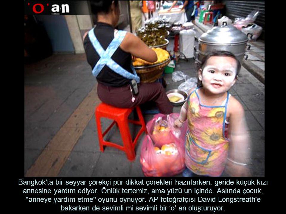 Bangkok'ta bir seyyar çörekçi pür dikkat çörekleri hazırlarken, geride küçük kızı annesine yardım ediyor.