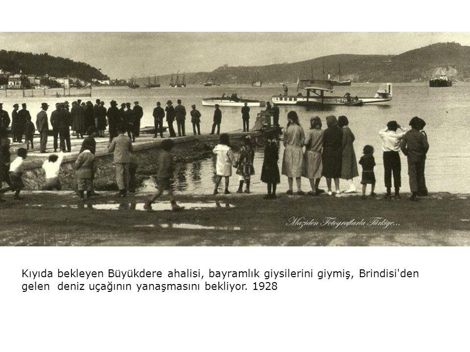 Kıyıda bekleyen Büyükdere ahalisi, bayramlık giysilerini giymiş, Brindisi den gelen deniz uçağının yanaşmasını bekliyor.