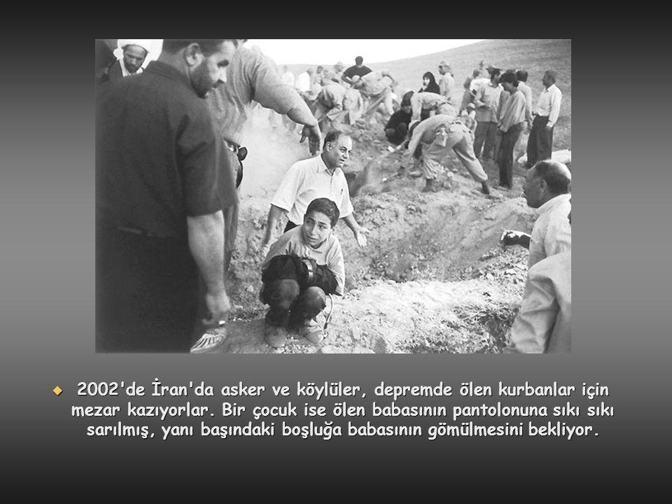 2002 de İran da asker ve köylüler, depremde ölen kurbanlar için mezar kazıyorlar.
