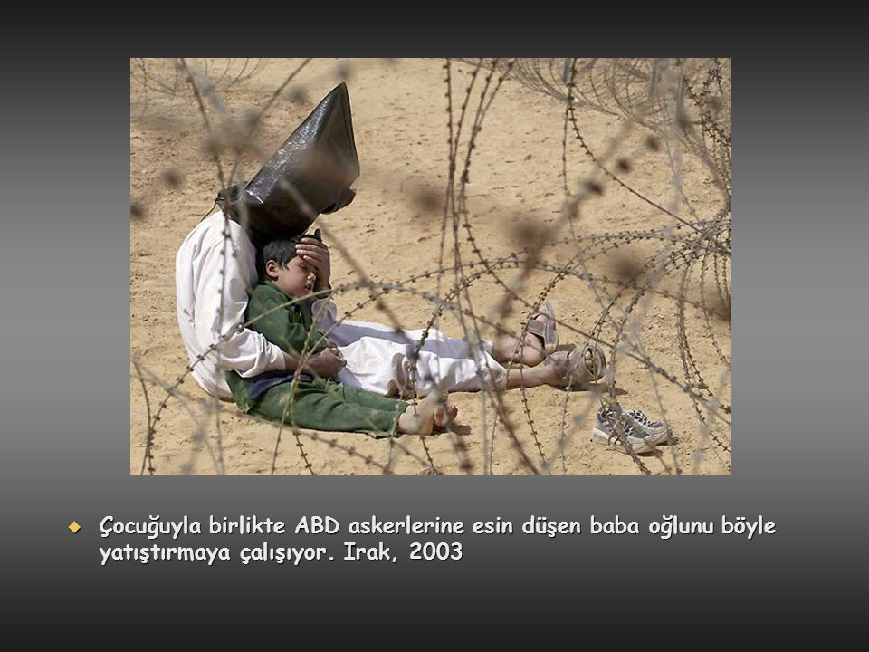 Çocuğuyla birlikte ABD askerlerine esin düşen baba oğlunu böyle yatıştırmaya çalışıyor. Irak, 2003