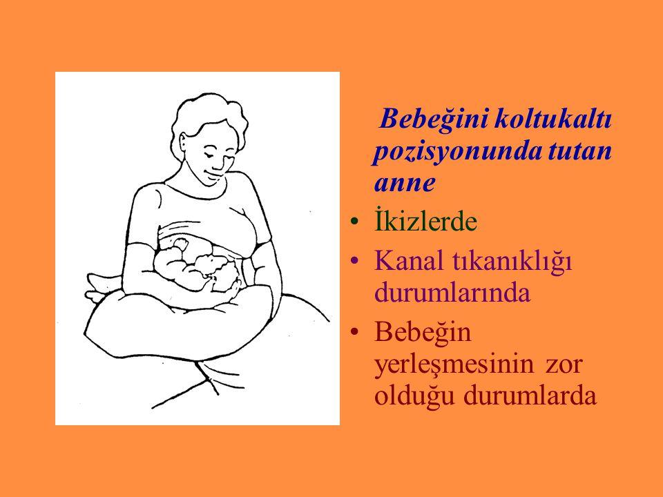 Bebeğini koltukaltı pozisyonunda tutan anne