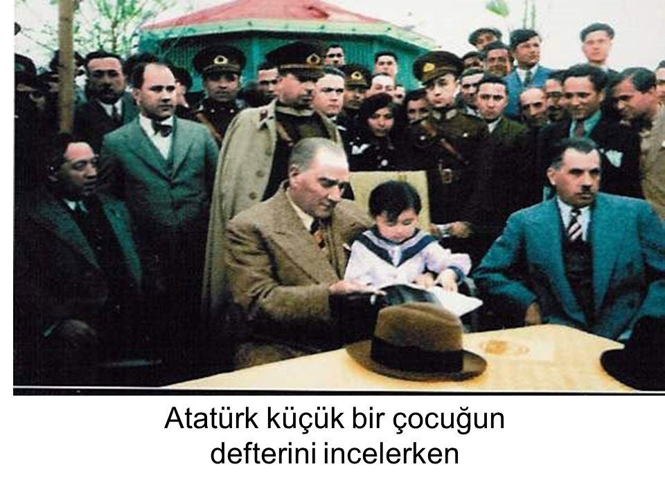 Atatürk küçük bir çocuğun defterini incelerken
