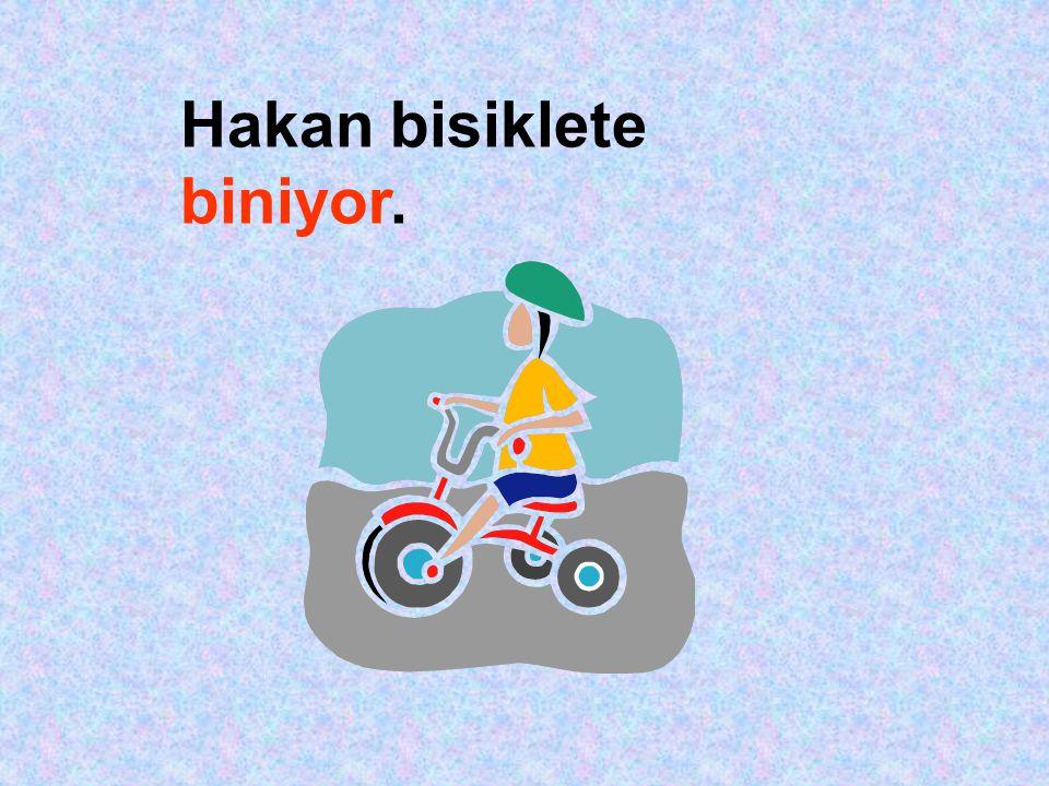Hakan bisiklete biniyor.