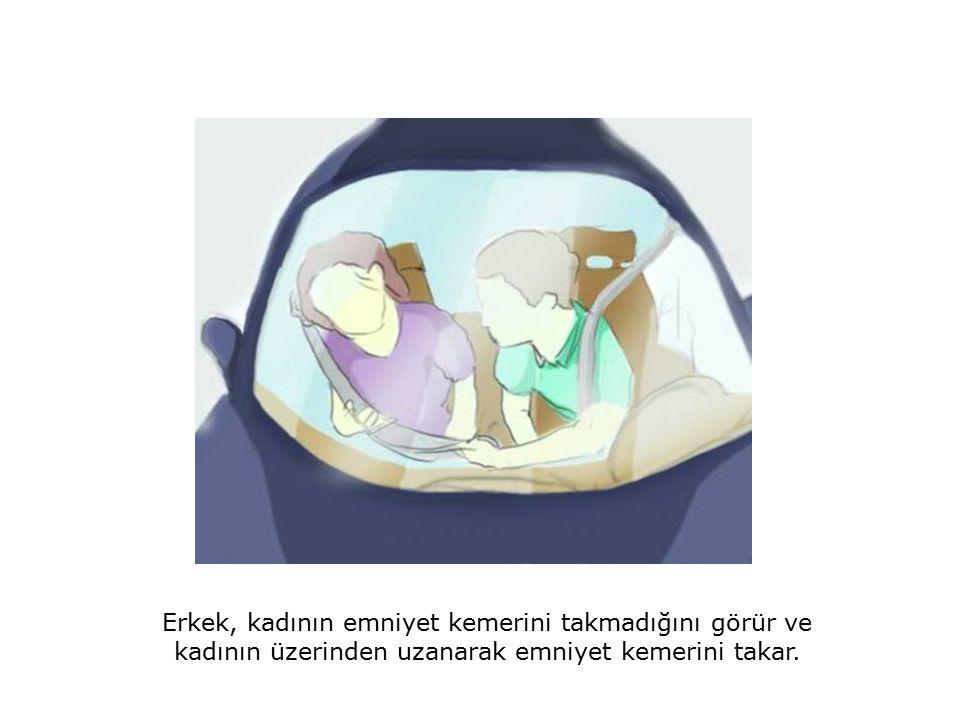 Erkek, kadının emniyet kemerini takmadığını görür ve kadının üzerinden uzanarak emniyet kemerini takar.