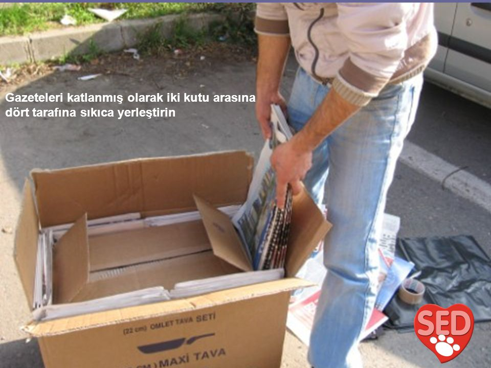 Gazeteleri katlanmış olarak iki kutu arasına