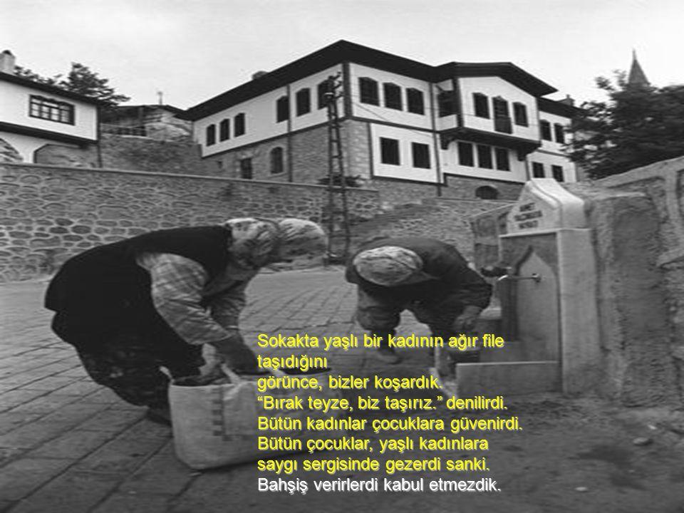 Sokakta yaşlı bir kadının ağır file taşıdığını