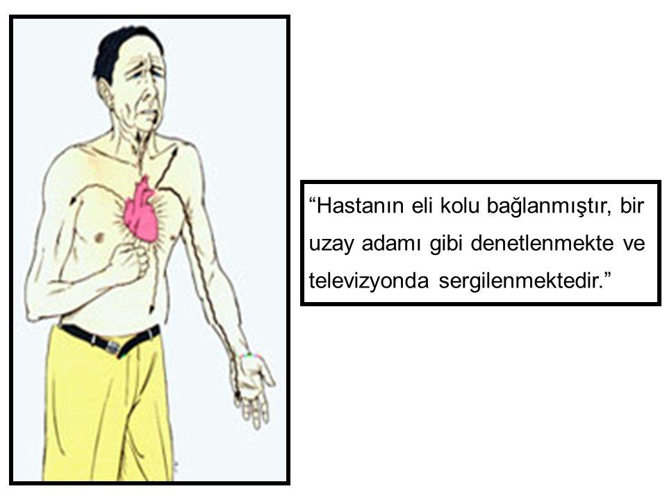 Hastanın eli kolu bağlanmıştır, bir uzay adamı gibi denetlenmekte ve televizyonda sergilenmektedir.