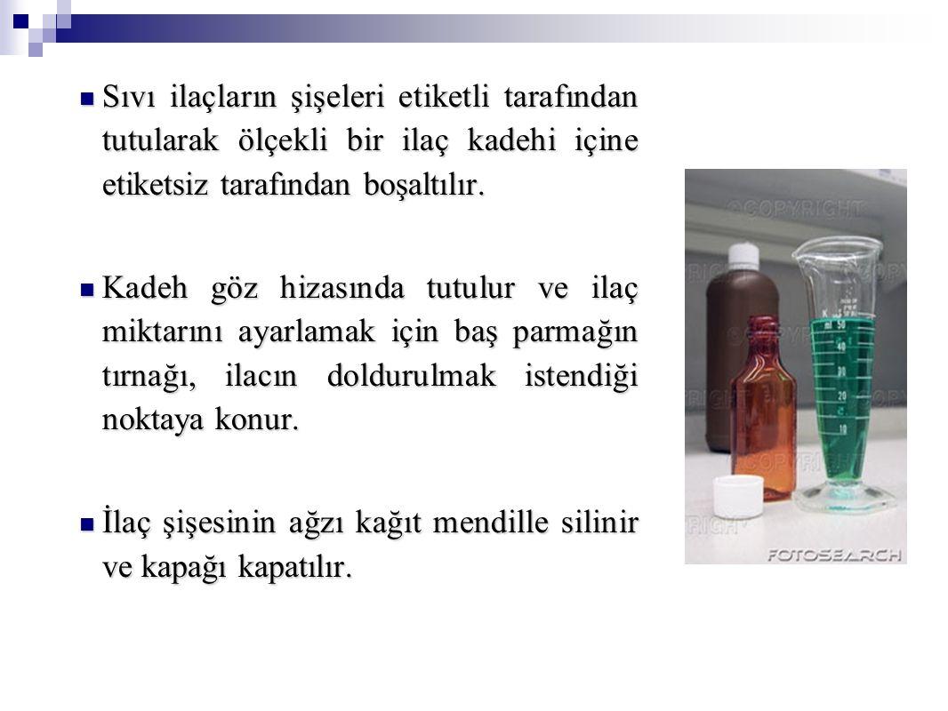 Sıvı ilaçların şişeleri etiketli tarafından tutularak ölçekli bir ilaç kadehi içine etiketsiz tarafından boşaltılır.