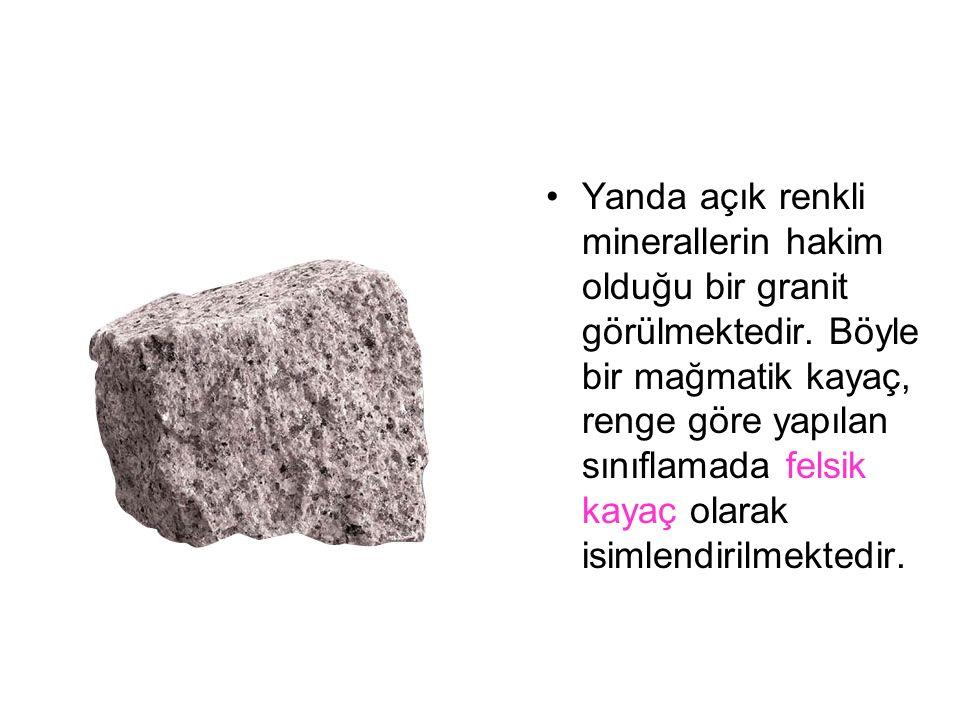 Yanda açık renkli minerallerin hakim olduğu bir granit görülmektedir